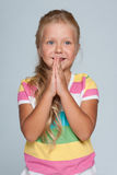Joyful little girl against the gray background Royalty Free Stock Images