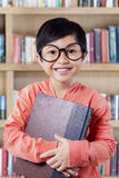 Joyful little girl with book smiling on the camera Royalty Free Stock Images