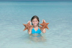 Joyful little girl caught two starfish in tranquil azure ocean Stock Photo