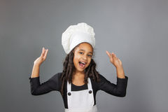 Joyful little girl chef showing ok sign. On a gray background Royalty Free Stock Photography