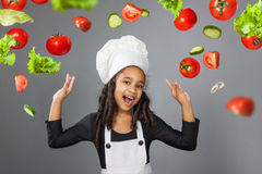 Joyful little girl chef showing ok sign. Vegetables fly Royalty Free Stock Images