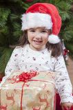 Joyful little girl child with her gift box under Christmas tree Royalty Free Stock Photo