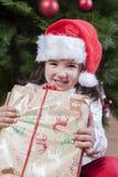 Joyful little girl child with her gift box under Christmas tree Stock Photo