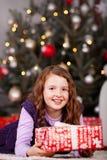 Joyful little girl with a Christmas gift Stock Photos