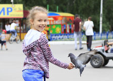 Joyful little girl with a dove Stock Image