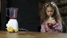 Joyful little girl drinking tasty berry smoothie stock video footage