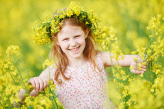 Joyful little girl with flower garland at yellow meadow Royalty Free Stock Photo