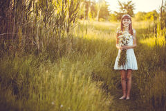 Joyful little girl on a green meadow with a bouquet of chamomiles Royalty Free Stock Photo