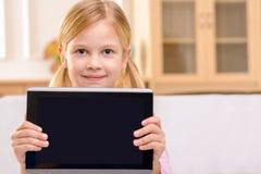 Joyful little girl holding tablet stock photos