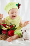 Joyful Little Girl In Greenish Clothes And Hat Sits On Bedding Royalty Free Stock Photos
