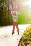 Joyful little girl jumping in the autumn park stock photography