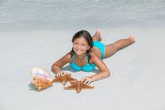 Joyful little girl lying on seashore white sand beach Royalty Free Stock Image
