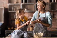 Joyful little girl mixing the pastry with her mother Royalty Free Stock Photo