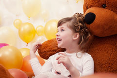 Joyful little girl posing hugging plush bear Stock Photo