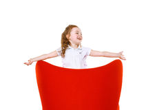 Joyful little girl in red chair Stock Images