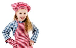 Joyful little girl in red apron isolated on white background. Joyful little girl in red plaid apron, chef hat and baking glove smiles isolated on white Stock Photography
