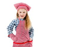 Joyful little girl in red apron isolated on white background. Joyful little girl in red plaid apron, chef hat and baking glove smiles isolated on white Stock Image