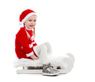 Joyful little girl in santa suit sitting on a sleigh Royalty Free Stock Images