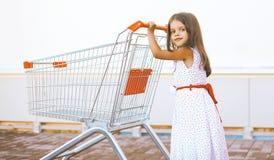Joyful little girl with shopping cart. Joyful little lady girl with shopping cart royalty free stock images