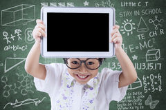 Joyful little girl showing tablet in class. Portrait of happy female elementary school student standing in the class while showing empty tablet screen Royalty Free Stock Photos