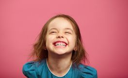 Joyful little girl sincere laughing at pink isolated background. stock images