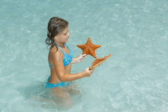 Joyful little girl sitting in azure crystal clear ocean and looking at starfish Stock Photos