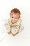 Joyful little girl sitting on bed and looking up at the camera Stock Images