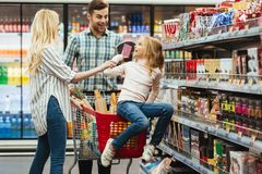 Joyful little girl sitting on a shopping cart. And choosing candy with her parents at the supermarket Royalty Free Stock Photos