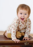 Joyful little girl sitting on a suitcase and smile Royalty Free Stock Images