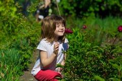 Joyful little girl sniff flowers Stock Image