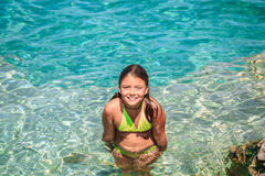 Joyful little girl standing in azure tranquil turquoise amazing Cyprus lake water, at Bruce Peninsula, Ontario Stock Photos
