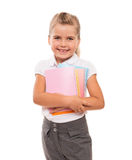 Joyful little girl standing on white with few colorful notebooks Stock Photos