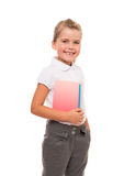 Joyful little girl standing on white with notebook and pencil Stock Photo