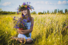 Joyful little girl on a sunset meadow with a Bouquet of wildflowers Royalty Free Stock Photography