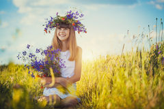 Joyful little girl on a sunset meadow with a Bouquet of wildflowers Royalty Free Stock Photos