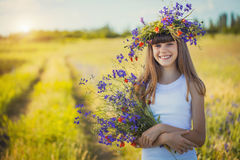 Joyful little girl on a sunset meadow with a Bouquet of wildflowers Stock Photography