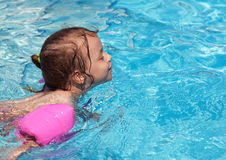 Joyful little girl swimming in the pool. Royalty Free Stock Photos