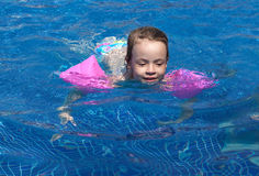 Joyful little girl swimming in the pool. Stock Images