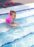 Joyful little girl swimming in the pool. Stock Photos