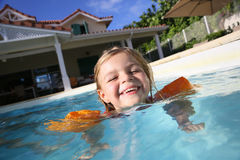Joyful little girl in the swimming pool having fun Stock Photos