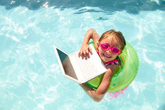 Joyful little girl swimming in pool with laptop. Portrait of joyful little girl wearing goggles swimming in pool with flotation ring holding laptop, looking at Royalty Free Stock Image
