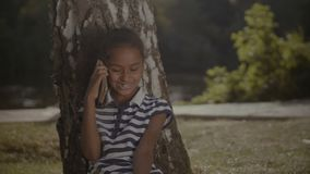 Joyful little girl talking on mobile phone under the tree. Portrait of joyful curly elementary age african american girl talking on cellphone while sitting under stock video