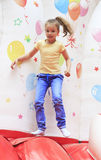 Joyful little girl on a trampoline. Royalty Free Stock Image