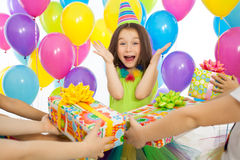Joyful little kid girl receiving gifts at birthday Stock Photos