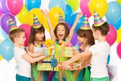 Joyful little kid girl receiving gifts at birthday Stock Photos