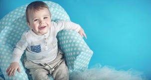 Joyful little man sitting on the comfortable armchair Stock Photos