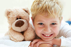 Joyful little one with teddy bear is happy and smiling. Stock Photos