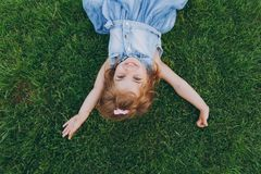 Joyful little pretty child baby girl in light dress lie on green grass lawn, spreading hands in park. Mother, little kid. Daughter. Mother`s Day, love family stock image