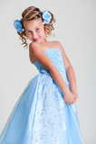 Joyful little princess. In blue dress posing against grey background Royalty Free Stock Image