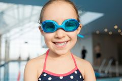 Joyful Little Swimmer with Toothy Smile. Head and shoulders portrait of cheerful little girl wearing swimsuit and goggles looking at camera with toothy smile Royalty Free Stock Images